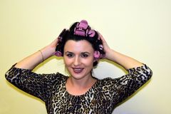 The young woman has the locks of hair which are reeled up on hair curlers. Royalty Free Stock Images