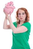 Young woman has money problems - isolated on green with piggy ba stock image