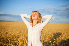 Young woman has pleasure time in grain field Royalty Free Stock Photo