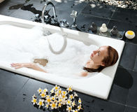 The young woman has a rest in a bathroom Stock Image