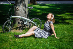 Young woman has rest near bicycle in the park Stock Photography