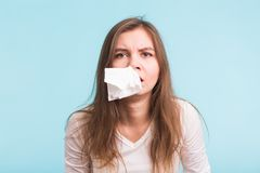 Young woman has a runny nose on blue background Stock Photography