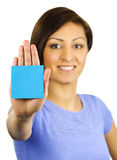 Young woman has a sticky note stuck on her hand. A pretty, young ethnic woman has a blue sticky note stuck on the palm of her hand royalty free stock images
