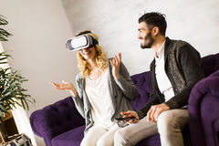 Young woman has a virtual reality glasses while man sitting. Young couple sitting in the room while  young women has a virtual reality glasses Stock Photography