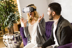 Young woman has a virtual reality glasses while man sitting. Young couple sitting in the room while  young women has a virtual reality glasses Royalty Free Stock Image