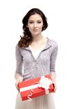 Young woman has a xmas gift. Wrapped in red paper, isolated on white Royalty Free Stock Photos