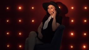 Young woman in hat against illuminated wall, talking using a smartphone. Portrait of dreamy woman in black dress and hat sitting on background of illuminated stock video footage