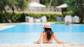 Young woman in bikini air mattress in the big swimming pool. Young woman in hat on an air mattress in a swimming pool. Vacation concept stock video footage