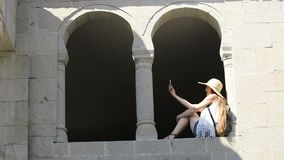 Young woman in a hat with a backpack makes selfie, sitting in the arch of an old window. Sunny summer day. Travels.  stock video footage