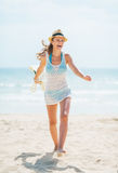 Young woman in hat and with bag having fun time on beach Stock Photos