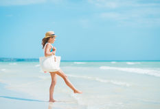 Young woman with hat and bag having fun time on sea coast Stock Images