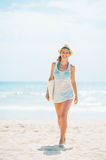 Young woman in hat and with bag walking on beach Royalty Free Stock Images