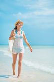 Young woman with hat and bag walking on sea coast Royalty Free Stock Photo