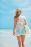 Young woman with hat and bag walking on sea shore Royalty Free Stock Photo