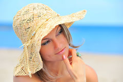 Young woman with hat on the beach Stock Images