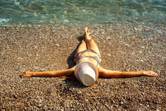 Young woman in a hat and bikini lying on the beach in hot summer Royalty Free Stock Photography