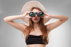 Young woman in hat with binoculars Stock Photo