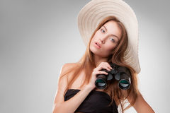 Young woman in hat with binoculars. Isolated on gray background. Travel and adventure concept. Closeup Royalty Free Stock Images