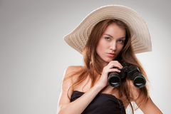 Young woman in hat with binoculars. Isolated on gray background. Travel and adventure concept. Closeup Stock Photography