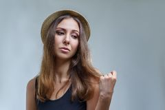 Young woman in hat and black shirt is proudly posing isolated on gray background in a studio close up