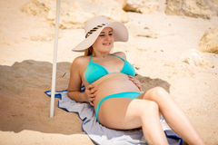 Young woman in hat and blue bikini relaxing on beach under paras Stock Image