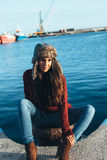 Young woman in hat and casual clothes sitting on pier. And looking away Stock Image