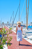 Young woman in hat and cute summer dress on the pier. Sailboat harbor. Royalty Free Stock Photography