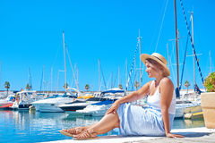 Young woman in hat and cute summer dress on the pier. Sailboat harbor. Royalty Free Stock Images