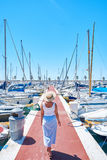 Young woman in hat and cute summer dress on the pier. Sailboat harbor. Stock Images