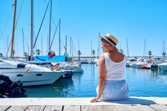 Young woman in hat and cute summer dress on the pier. Sailboat harbor. Royalty Free Stock Photo