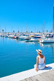 Young woman in hat and cute summer dress on the pier. Sailboat harbor. Stock Photo