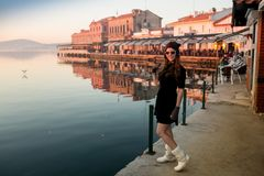 Young woman in hat and cute summer dress standing on the pier with peaceful town scenery, looking at sunset Royalty Free Stock Images