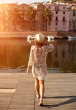 Young woman in hat and cute summer dress standing on the pier with peaceful town scenery, looking at sunset Stock Image
