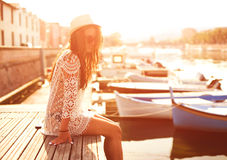 Young woman in hat and cute summer dress standing on the pier with peaceful town scenery, looking at sunset Royalty Free Stock Image