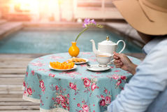 Young woman with hat drinking tea with biscuit and orange fruit Royalty Free Stock Image