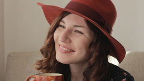 Young woman in hat drinks coffee stock video