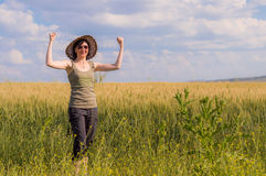 Young woman with hat enjoying the nature. Victory concept. Caucasian woman with arms raised celebrating her success in a field on a summer day Stock Photography