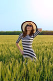 Young woman in a hat in a field, bright summer photo. Beautiful woman in sunglasses and hat. Girl in the sea dress. Sport Lady Royalty Free Stock Photography