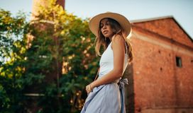 Young woman in hat goes at city street next to building and tree royalty free stock photos