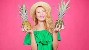 Young woman in hat holding a pineapple on a pink background. Happy young woman in hat holding a pineapple on a pink background stock video