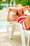 Young woman in hat laying on chaise-longue Stock Images