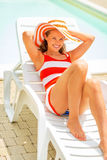 Young woman in hat laying on sunbed Stock Photography