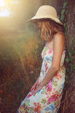Young woman with hat leaning to a tree Stock Photography
