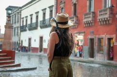 Young woman in hat looking at rain storm at town square of San Miguel de Allende. El Jardin in historic center of San Miguel de Allende during rain storm, with stock photography