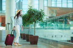 Young woman in hat with luggage in international airport. Airline passenger in an airport lounge waiting for flight Royalty Free Stock Image