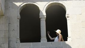 Young woman in a hat makes selfie, sitting in the arch of an old window. Sunny summer day. Travels.  stock video