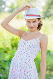 Young Woman with a Hat in the Park Royalty Free Stock Photography