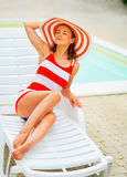 Young woman in hat relaxing on sunbed Stock Images