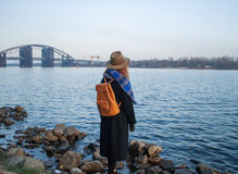 Young woman in hat and with rucksack standing on the riverbank, looking at sunset or sunrise horizon, back view Royalty Free Stock Photos