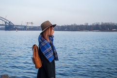Young woman in hat and with rucksack standing on the riverbank, looking at sunset or sunrise horizon, back view Royalty Free Stock Photo